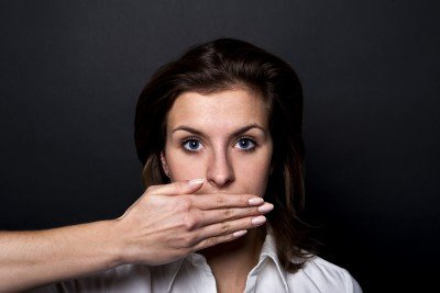 woman with hand hiding her mouth and emotions
